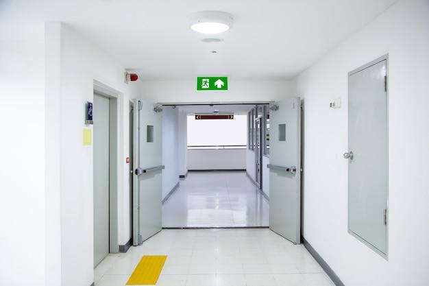 문 출구와 함께 녹색 화재 출구 표지판을 닫습니다.