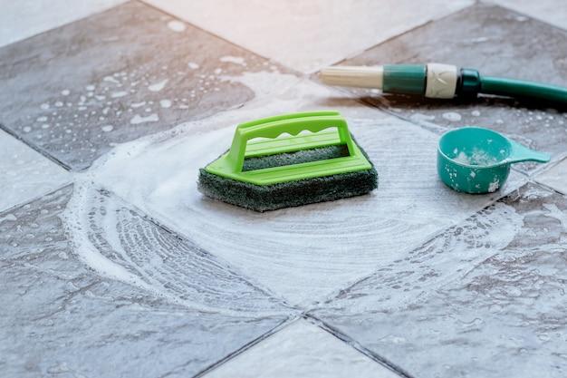 床をこすり洗いするために緑色のプラスチックブラシを閉じて、濡れたタイルの床に置き、洗剤で泡立てます。