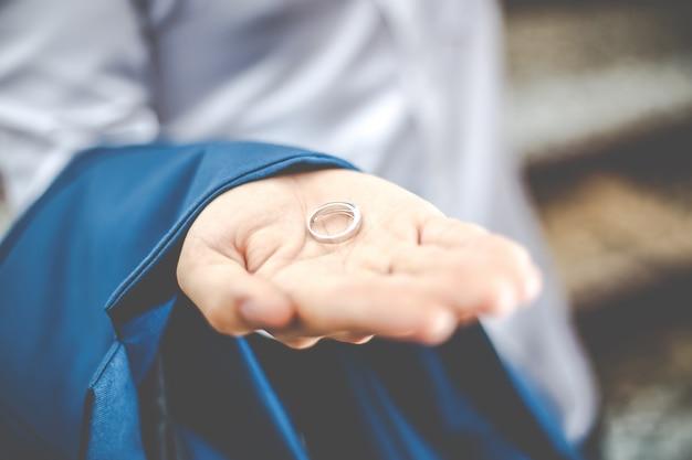手のひらに結婚指輪を持って新郎をクローズアップ。