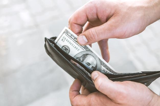 Крупный план, парень держит в руке бумажник с деньгами.