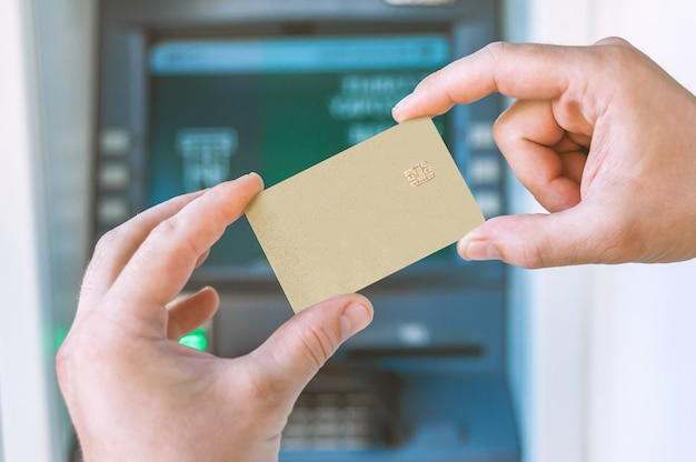 클로즈업, 그 남자는 atm 앞에서 은행 카드를 손에 들고 있습니다.