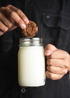 Закройте мужскую руку, держащую стакан молока и одно печенье, чтобы смешать с молоком