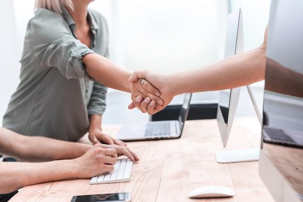 Закройте вверх. менеджер приветствует клиента рукопожатием. бизнес-концепция