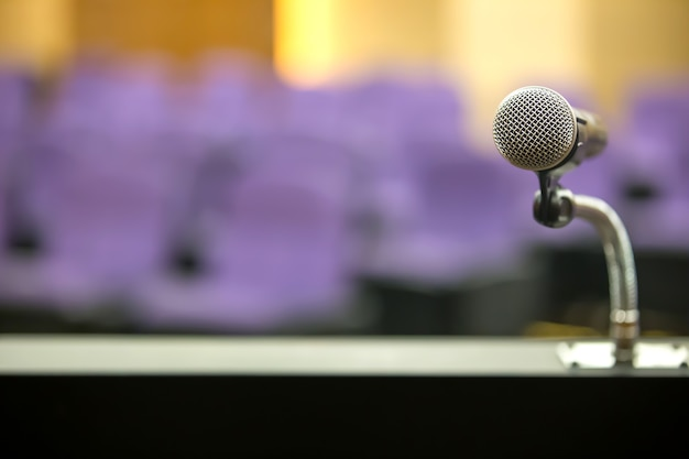 Крупным планом микрофон стоит на стенде с зрительным залом.