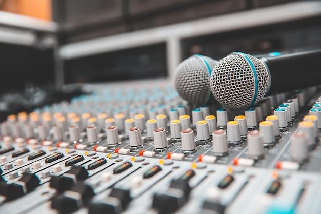 Крупный план микрофона размещен на профессиональном аудио микшере.
