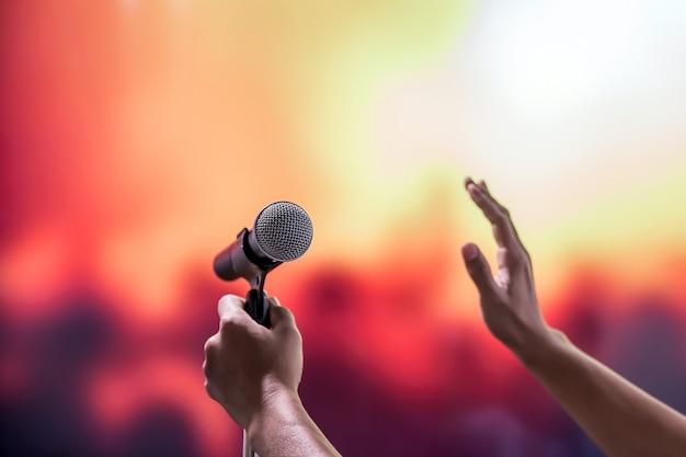 Крупным планом микрофон на подставке с размытым фоном.
