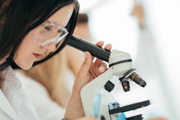 닫기 up.the 과학자는 실험실에서 현미경으로 보인다. 과학과 건강