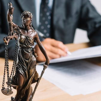 Close-up of themis or lady justice holding scale in front of lawyer working at desk