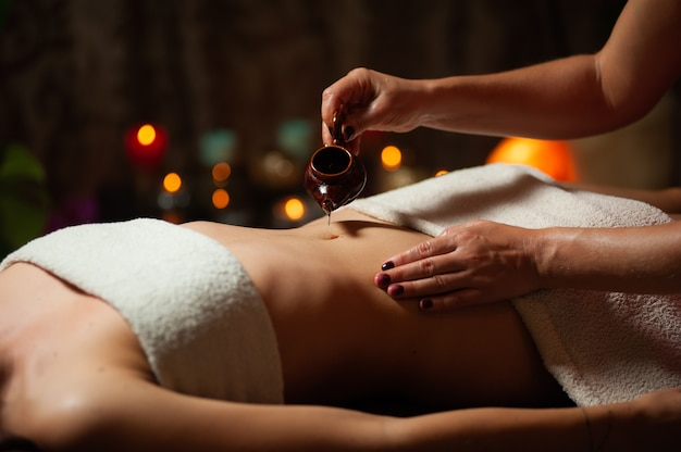 Close up of therapist doing stomach massage on woman in spa against dark.