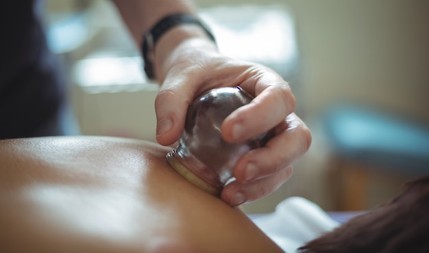 Close up of therapist giving cupping therapy to man