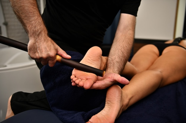 Close up of therapist hands massaging female legs with bamboo stick. thai foot massage at the spa salon