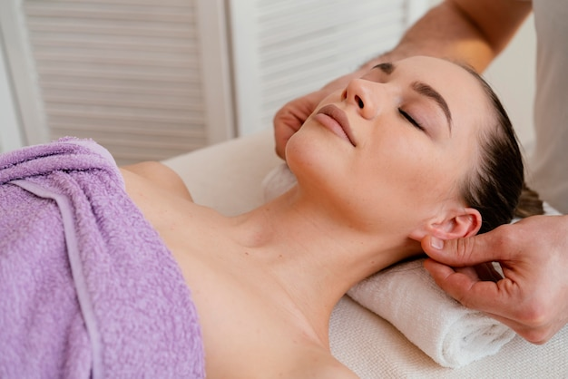 Close up therapist massaging ears