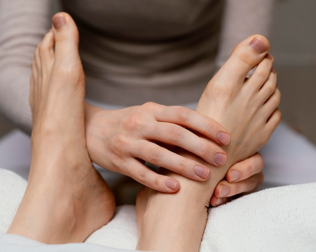 Primo piano terapista che massaggia il piede