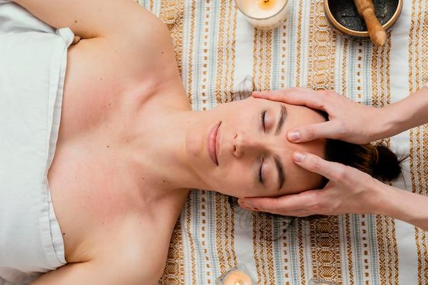 Close up therapist massaging forehead