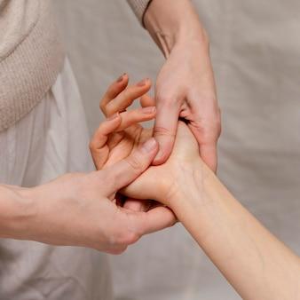 Primo piano terapista che massaggia il palmo