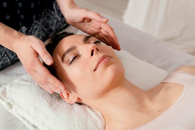 Primo piano terapista che massaggia le orecchie del paziente