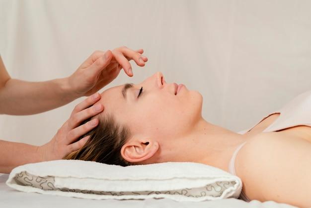 Primo piano terapista che massaggia la testa del paziente