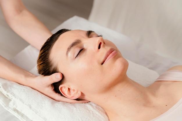 Primo piano terapista che massaggia il cuoio capelluto del paziente
