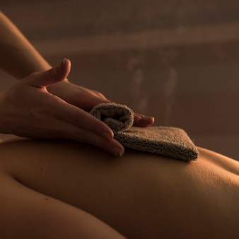 Close-up of a therapist massaging woman's back with hot towel in beauty spa