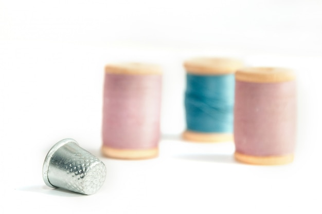 Close up thimble with spools of thread in soft focus isolated on white background