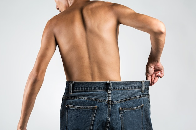Close up thin asian young man pulling his biggest jeans