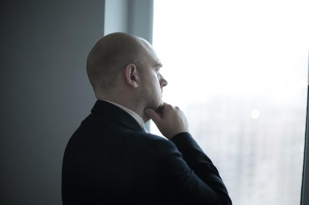 Закройте вверх. вдумчивый бизнесмен смотрит в окно офиса