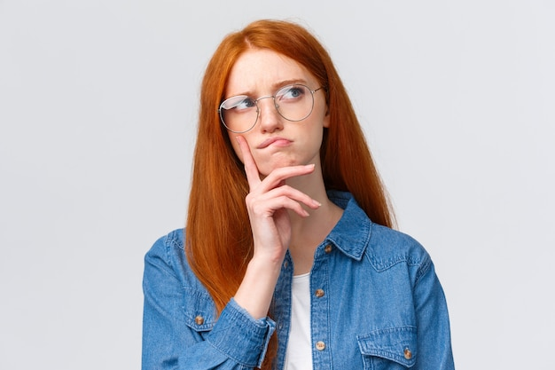 Close-up thoughtful and focused, creative female freelancer, student want work part-time, thinking opportunities, look away smirk and frowning pondering, make decision, stand white
