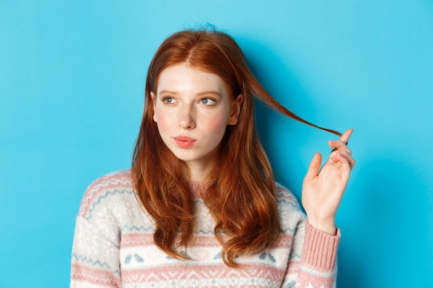 Close-up of thoughtful pretty redhead girl looking left, playing with hair strand and pondering, standing in winter sweater against blue background