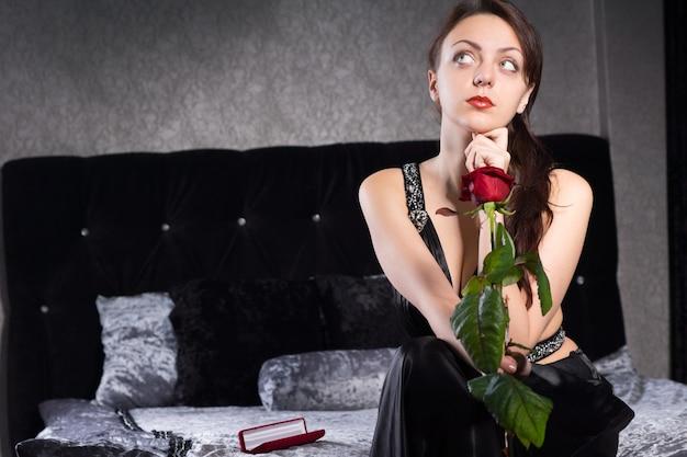 Заделывают задумчивая красотка в ее спальне с свежим цветком красной розы