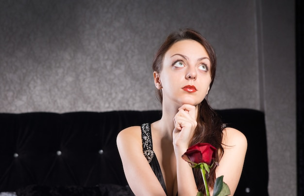Закройте вдумчивую симпатичную молодую леди с цветком красной розы, глядя вверх.