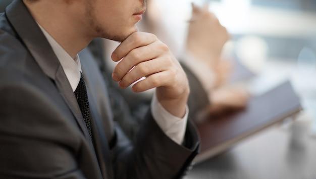 クローズアップ。彼の机に座っている思いやりのある青年実業家。ビジネスコンセプト。