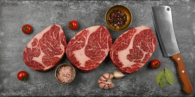 석재 탁자 위에 칼과 향신료를 넣은 세 개의 마블링된 생 리브아이 쇠고기 스테이크를 닫습니다