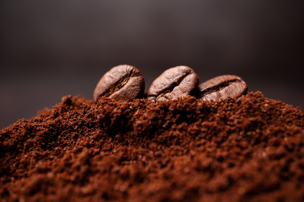 Close up of three coffee beans at the mixed heap of roasted coffee
