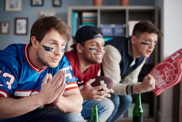 Primo piano di tre fan che indossano abiti sportivi