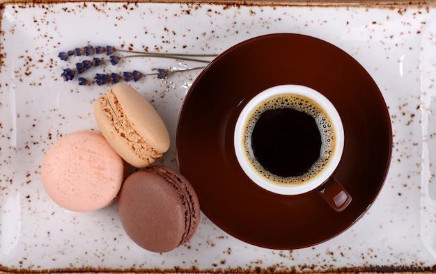 Закройте три французских печенья макарун и чашку черного кофе на коричневом блюдце и деревенской фарфоровой тарелке, вид сверху, прямо над