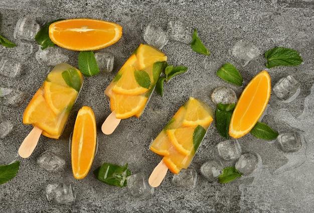 신선한 오렌지 조각, 녹색 민트 잎, 얼음 조각으로 세 개의 과일 아이스크림 아이스 캔디를 닫습니다