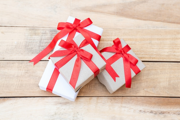 Close up three gift boxes. red ribbon bow with gift boxes on wooden table, wrapped vintage box with copy space
