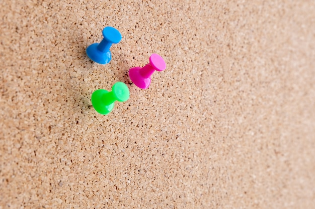 Close up of three push pins on a cork message board
