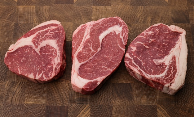 커팅 보드에 3개의 원시 마블 립아이 쇠고기 스테이크를 닫습니다