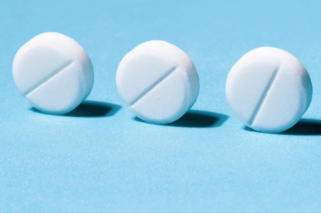 Close up three round tablets on a blue background