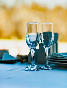 クローズアップ3つのワイングラスは、晴れた冬の日に自然のぼやけた景色を望む窓の背景に対してテーブルの上に立っています。冬のリラクゼーションとロマンチックな旅行の概念