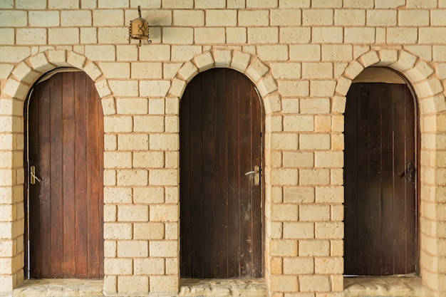 Close up of three wooden doors and white brick wall