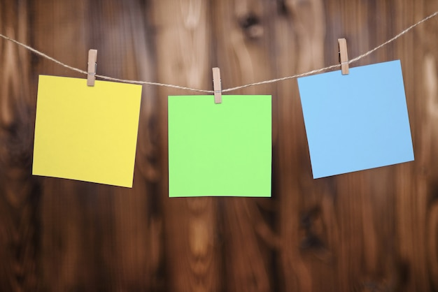 Close up of three yellow green and blue note papers hung by wooden clothes pegs on a brown wooden background