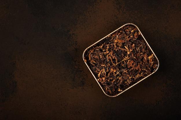 Крупным планом олово, полное готовой протертой смеси длинного грубого трубочного табака на коричневом гранж-фоне, вид сверху, прямо над