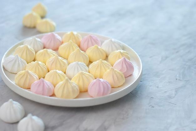 Макро крошечные безе розового, белого и желтого цветов в белой миске на белом светло-сером столе