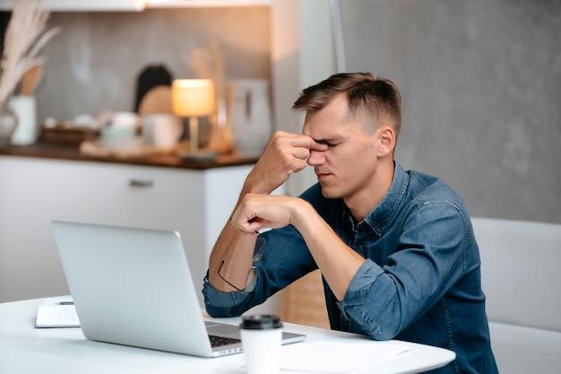 閉じる。疲れた男はホームオフィスで働いています。人とテクノロジー。
