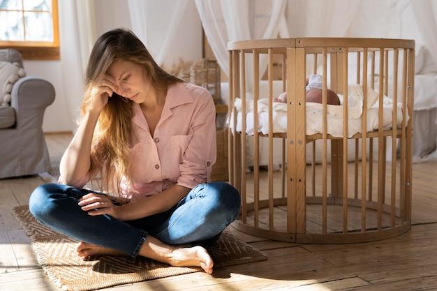Primo piano sulla mamma stanca che si prende cura del neonato