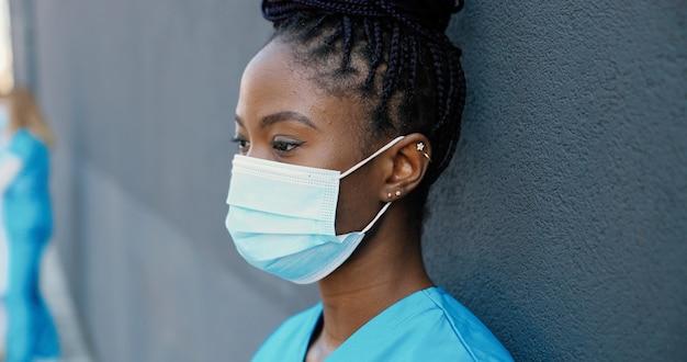 의료 마스크를 벗고 휴식 하 고 야외 벽에 기대어 동안 뜨거운 음료를 마시 며 피곤 된 젊은 아프리카 계 미국인 여자 의사를 닫습니다. 예쁜 여성 간호사 마시는 커피와 휴식 후 열심히