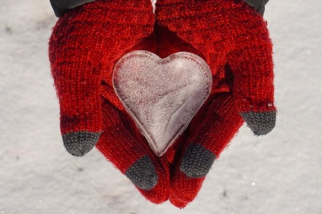 Крупным планом ледяное сердце в руках в перчатках