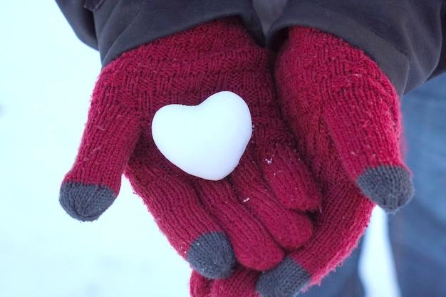 Крупный план сердца снежный ком в руках женщины